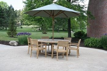 A round wooden table and chairs with a patio umbrella set in an open area with flowers and grassy fi